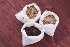 Pale, caramel, chocolate malt in a bags. Craft beer brewing from. Grain barley malt in process. Ale or lager from pale or dark pilsner malt. wooden background Royalty Free Stock Photo