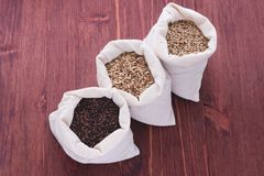 Pale, caramel, chocolate malt in a bags. Craft beer brewing from. Grain barley malt in process. Ale or lager from pale or dark pilsner malt. wooden background Royalty Free Stock Image