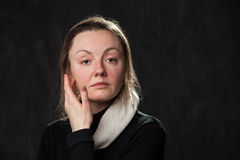 Pale confused woman touching her face. On grey background royalty free stock photo