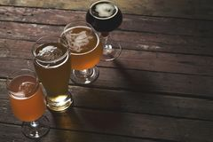 Four sorts of beer. Pale, dark, unfiltered pale and red fruit beer in four different beer glasses on a rustic wooden table. Selective focus Stock Images