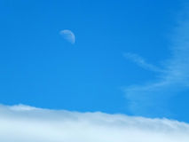 Pale daytime moon. In blue summer sky above the clouds Royalty Free Stock Photography