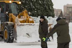Pale dei lavoratori per rimuovere la neve sulla città del ghiaccio immagini stock libere da diritti