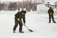 Pale dei lavoratori per rimuovere la neve sulla città del ghiaccio fotografie stock
