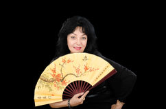 Pale faced mature woman with fan Royalty Free Stock Photography