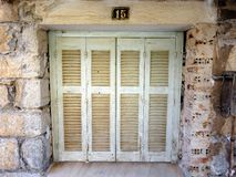 Pale Green Window Shutters. Closed faded pale green painted wooden shutters on old Greek stone and brick building. A generic image but actual location is Itea Stock Image
