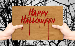 Pale hand holding wood plate with Happy Halloween blood type on Stock Photography