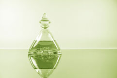 Pale lime perfume on mirror surface Stock Images