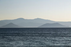 Pale mountain chain in a blue ocean Royalty Free Stock Image