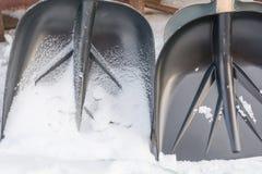 Pale per pulizia della neve Un supporto di due pale nella neve fotografie stock