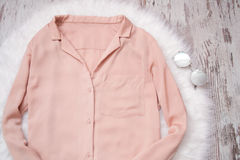 Pale pink blouse on a white fur glasses. Fashionable concept, top view.  Stock Photos