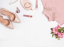Pale pink feminine accessories and flowers on the white background. Stylish flat lay royalty free stock photography
