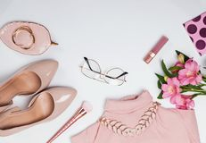 Pale pink feminine accessories and flowers on the white background. Stylish flat lay stock images