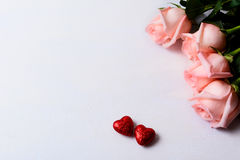 Pale pink roses and red glitter hearts Stock Photos