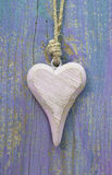 Pale pink rustic wooden heart on purple wooden surface for greet Royalty Free Stock Image