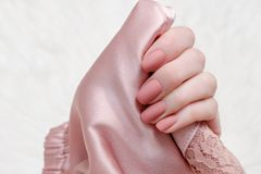 Pale pink satin textile in female hand. Beauty manicure. Fashion. Able concept Stock Photos