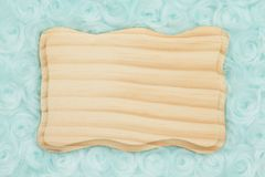 Pale teal rose plush fabric with wood plaque background. Pale teal rose plush fabric background with wood plaque to provide copy-space for your message stock images