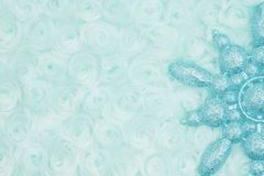 Pale teal snowflake on swirl plush fabric background. With muted mix of shades to provide copy-space for your message royalty free stock photo
