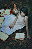 Pale woman and books in a dark forest. Surreal and halloween royalty free stock image