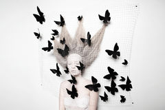 Pale woman in cocoon with butterflies Stock Photos