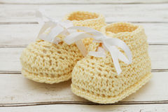 Pale Yellow Baby Booties on wood background Stock Photos