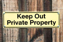 Pale Yellow and Black Sign Stating Keep Out Private Property Royalty Free Stock Photo