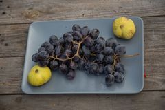 Pale yellow figs and a bunch of grapes on a gray plate on a wooden table top, royalty free stock images