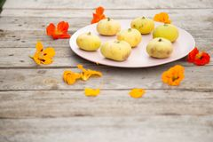 Pale yellow figs on a pink plate stock image