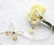 Pale yellow flowers with butterfly on embossed background. Bunch of narcissus tied with a ribbon and a clearwing butterfly on embossed art paper Stock Image