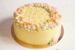 Pale yellow mousse cake with pastel cream flowers Royalty Free Stock Photography
