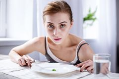 Pale young woman looking at you. At breakfast. Pale young woman looking at you while eating her breakfast stock photo