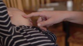 Palec macierzysta dotyk twarz mały dziecko podczas łasowania zbiory