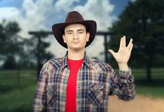Paleface young cowboy showing Spoke sign Royalty Free Stock Photo
