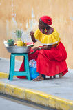 Palenquera woman sells fruits. CARTAGENA, MAY 13: Palenquera woman with typical dress sells fruit on the Street on May 13, 2010 in Cartagena, Colombia Stock Photos