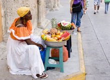 Palenquera Woman Sells Fruits. Palenquera woman with typical dress sells fruit on the Street on June 6 2009 in Cartagena Colombia. Palenqueras are a unique royalty free stock images