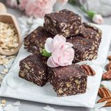 Paleo巧克力强身糕用燕麦片、山核桃果、日期、chia种子和椰子剥落,正方形 库存照片