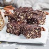 Paleo巧克力强身糕用燕麦片、山核桃果、日期、chia种子和椰子剥落,正方形 库存图片