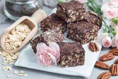 Paleo巧克力强身糕用燕麦片、山核桃果、日期、chia种子和椰子剥落,水平 免版税库存图片