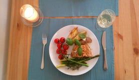 Paleo晚餐用蕃茄、芦笋potatos和三文鱼 免版税库存图片