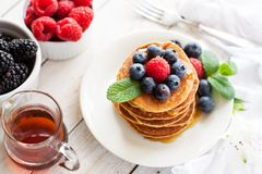 Paleo apple-cinnamon pancakes with berries, maple syrup royalty free stock image