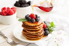 Paleo apple-cinnamon pancakes with berries, maple syrup. Stack of delicious paleo apple-cinnamon pancakes served with fresh berries, mint and maple syrup royalty free stock photos