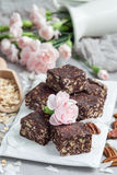 Paleo chocolate energy bars with rolled oats, pecan nuts, dates, chia seeds and coconut flakes Stock Image