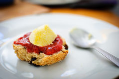 Paleo Diet Fruit Scone. A delicious Paleo diet friendly fruit scone with Strawberry and Raspberry Jam, and a dollop of Grass-fed Clotted cream Royalty Free Stock Photography