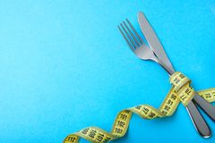 Paleo diet for weight loss. The fork and knife are wrapped in yellow measuring tape on blue. Background royalty free stock image