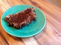 Paleo, reifes Brot des strengen Vegetariers überstieg mit Marmite, auf grüner Platte Lizenzfreie Stockbilder