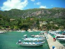 Paleokastritsa,科孚岛,希腊- 2013年6月07日:走在有Paleokastritsa hils的小船码头的游人在背景中 免版税图库摄影