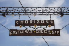 Paleokastritsa, Cofru, Greece- MAY 10, 2018 Hanging welcome signage of Horizon Restaurant Cocktail Bar. The wooden post with metal Royalty Free Stock Photo