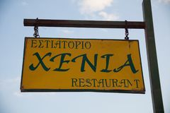 Paleokastritsa, Cofru, Greece- MAY 10, 2018Restaurant wooden hanging sing post. Yellow board with black letters chained to a brown royalty free stock photo