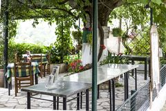Paleokastritsa Cofru, Grekland MAY 10 2018 insidablickar av Taverna den grekiska restaurangen med tabeller och stolar med trädgår Royaltyfria Bilder
