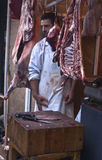Butcher sells meat on the local market. PALERMO - DECEMBER 29: butcher sells meat on the local market in Palermo, called Ballaro. This market is also tourist Royalty Free Stock Photography