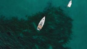 Palermo, SICILY, Italy - August 2019: Sailing boat with solar panels in the turquoise water of the ocean. The camera is. Looking down. Renewable energy concept stock video